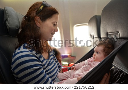 Mother carry her infant baby during flight.Concept photo of air travel with baby. - stock photo
