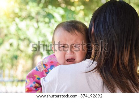 Mother carrying and comfort her daughter  crying, irritable and fever after vaccination.  - stock photo
