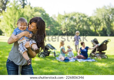 Mother carrying cheerful baby boy with friends and children in background at park - stock photo