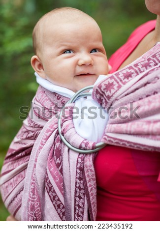 Mother carrying her child in a baby sling - stock photo