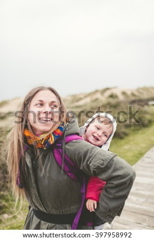 Mother carrying her child in a backpack outdoors in a cloudy day - stock photo