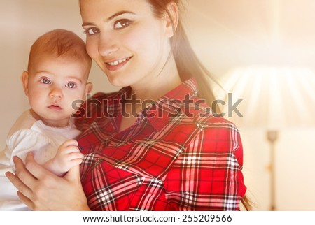 Mother carrying her little baby girl in her arms. - stock photo