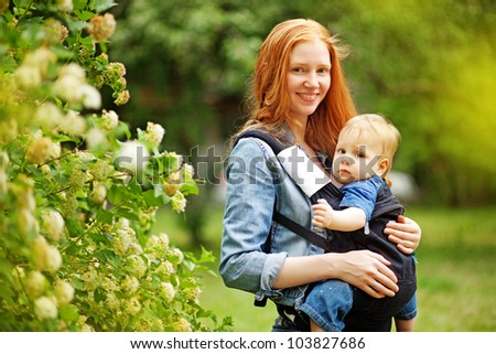 mother carrying son in sling in park - stock photo