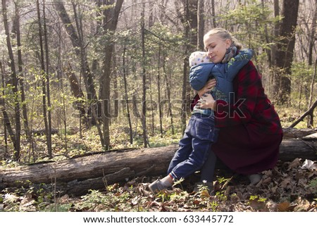 Mother Caucasian (European) appearance in a red checkered coat gently and carefully embracing her son; They are in the autumn (spring) warm sun forest; Day clear and bright