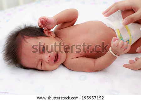Mother changing a diaper, 27 days after birth - stock photo