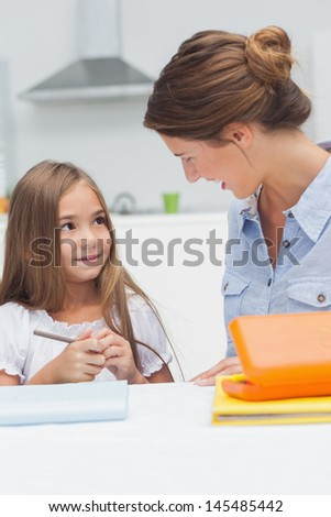 Mother chatting with her daughter drawing in the kitchen - stock photo
