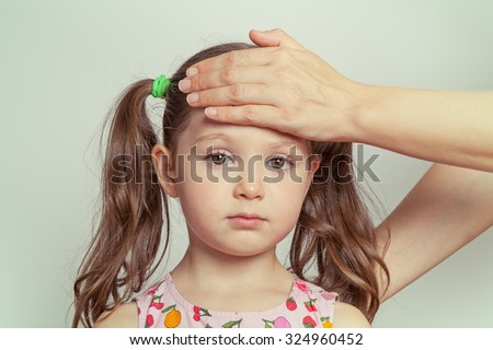 mother checking temperature of cute little sick girl - stock photo