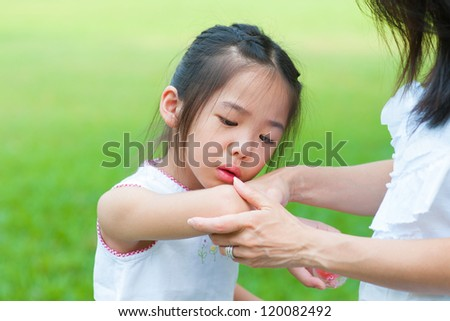 Mother checking wound to her daughter at outdoor park - stock photo
