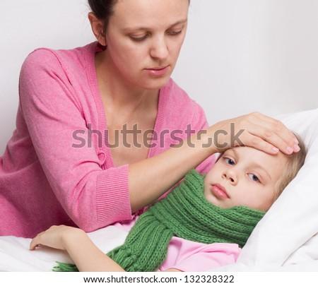 Mother checks the temperature of a sick girl - stock photo
