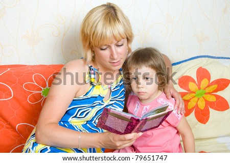 mother child reading a book, interior - stock photo