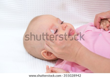 Mother cleaning baby's eyes isolated - stock photo