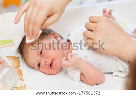 Mother cleaning newborn baby skin. - stock photo