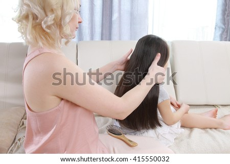 Mother combing daughter hair braids plait  - stock photo
