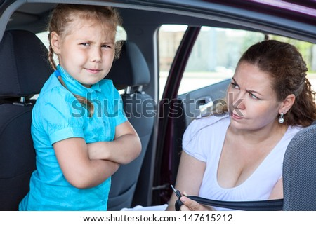 Mother convincing a girl to get in child safety seat against the wishes - stock photo