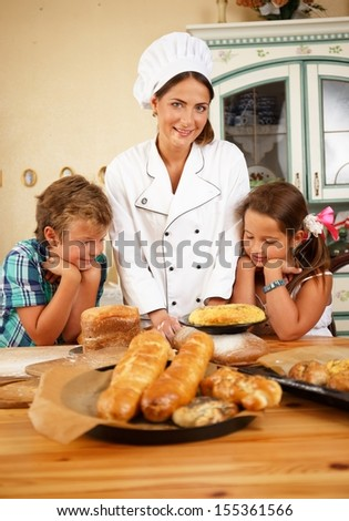 Mother cook with her little children preparing homemade pastry - stock photo