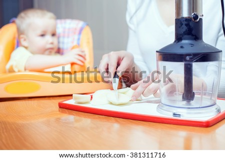 Mother cooking in blender, preparation of baby food. Pure. Food for baby. Baby care, healthy nutrition, meal. Child sitting on highchair at table. Kitchen, home. Fresh fruit, apple on the table - stock photo