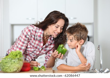 Mother cooking with son in kitchen - stock photo
