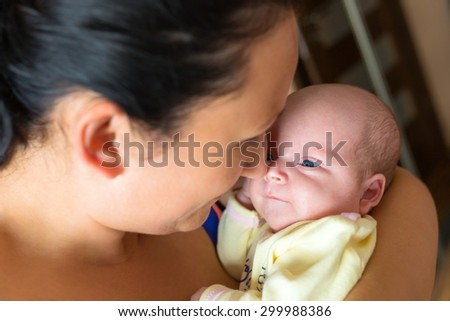 Mother cuddling her baby girl in arms - stock photo