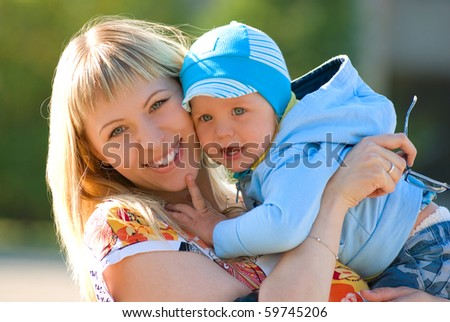 Mother cuddling young son, outdoor portraits - stock photo