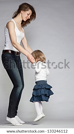 Mother dancing with her little daughter, grey background - stock photo