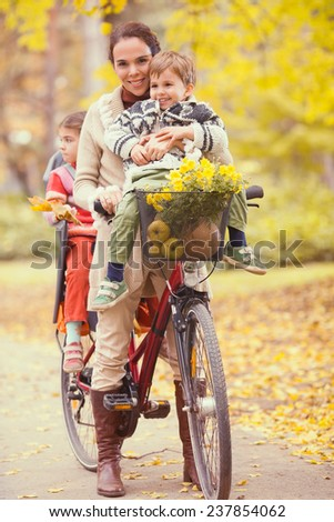 Mother, daughter and son on a bicycle in a park on a beautiful autumn day - stock photo