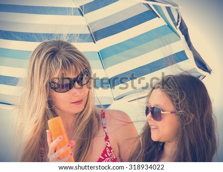 Mother, daughter and sunscreen - stock photo