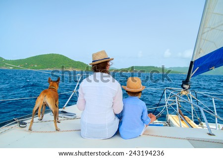 Mother, daughter and their pet dog sailing on a luxury yacht or catamaran boat - stock photo