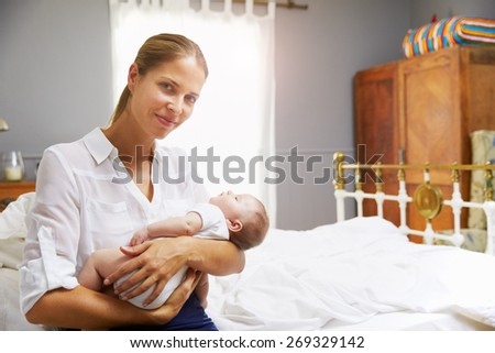 Mother Dressed For Work Holding Baby In Bedroom - stock photo