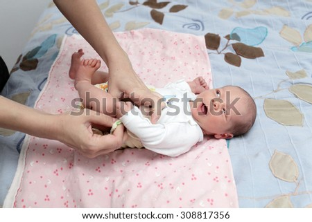 Mother dressing her hewborn baby on a bed - stock photo
