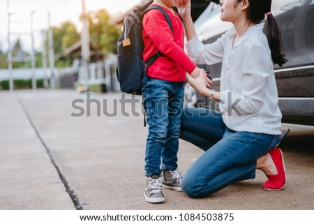 Mother dressing up a son and sending to school, Parent and pupil going to kindergarten of preschool first day back to school concept.