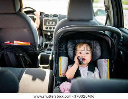Mother driving car and child sitting on back seat and playing with mobile phone