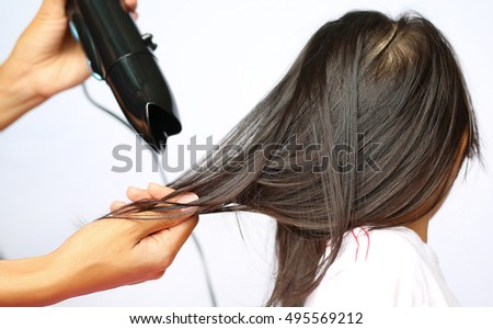 Mother drying hair of her child girl on white background