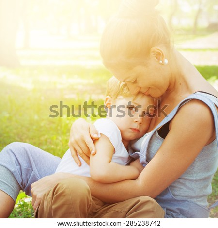 Mother Embraces her Son in Sun lights. Family in a Spring Park on Picnic.  - stock photo