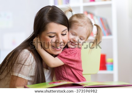 mother  embracing and reading  a book to kid at home - stock photo