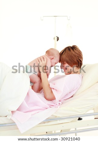 Mother embracing her newborn baby in hospital - stock photo