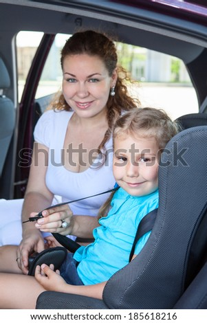 Mother fastening little daughter into infant safety seat in car - stock photo