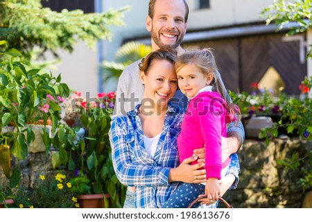 Mother, father and daughter in garden with basket - stock photo