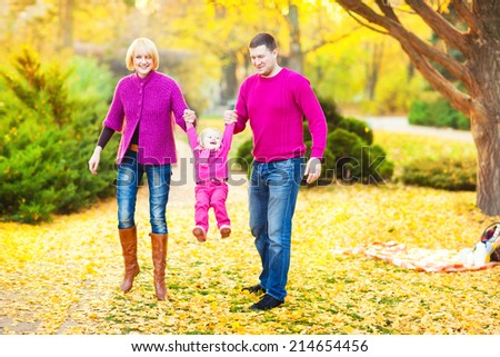 Mother, father  and daughter in the autumn nature. Beautiful family. - stock photo