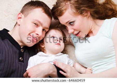 Mother, father and daughter lying - stock photo