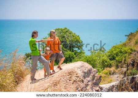 Mother, father and daughter stay on tropical island cliff and look at sea