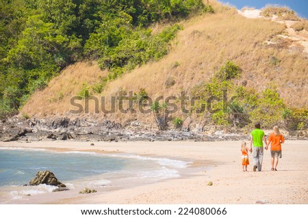 Mother, father and daughter walk along tropical beach holding hands - stock photo