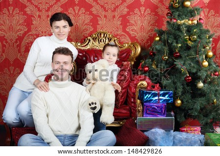 Mother, father and daughter with teddy bear and smile near Christmas tree at home. - stock photo