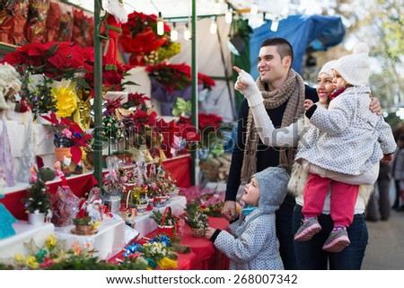 Mother, father and little children buying red Euphorbia at Christmas fair. Focus on woman - stock photo