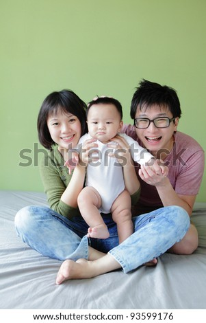 Mother, father and small baby smile face with green background. Model are asian family. - stock photo