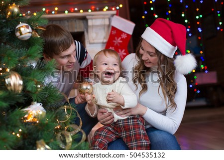 Mother, father and son decorating Christmas tree in living room