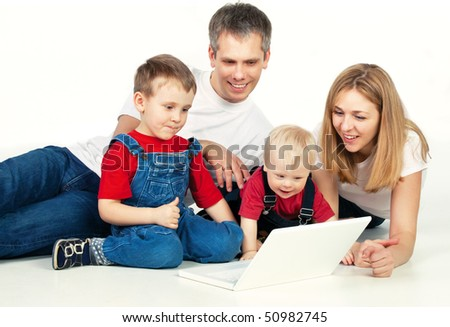 Mother, father and son lying on the floor with laptop - stock photo