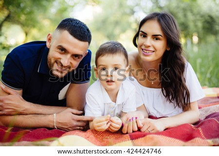 Mother, father and son lying on the grass in park on picnic. Summer family holiday - stock photo