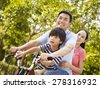 mother father and son riding a bicycle together outdoors in a  city park. - stock photo