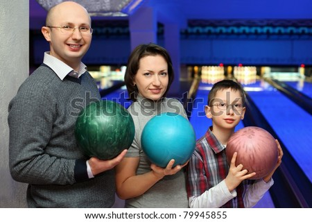 Mother, father and son, stand alongside and hold balls for bowling, focus on son - stock photo