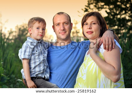 Mother, father and son together outdoors. Shallow DOF. - stock photo